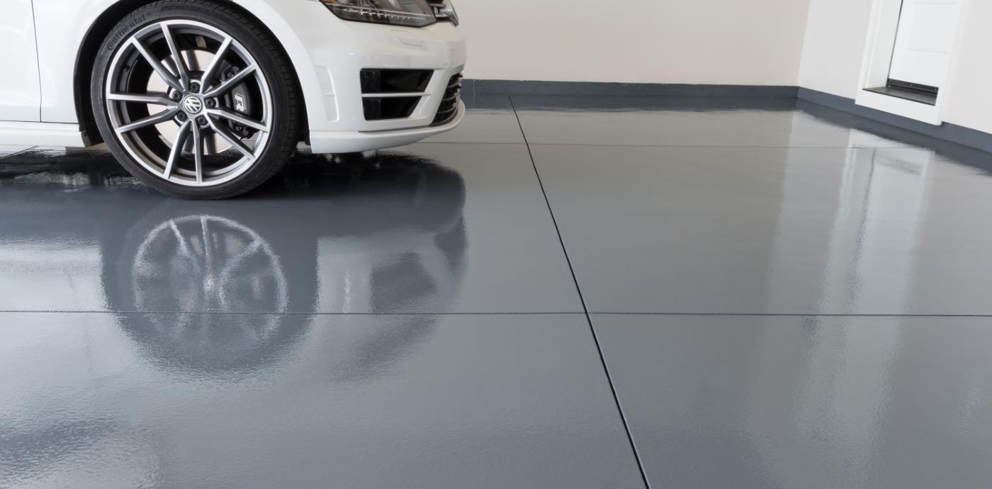 white car in garage with grey epoxied garage floor